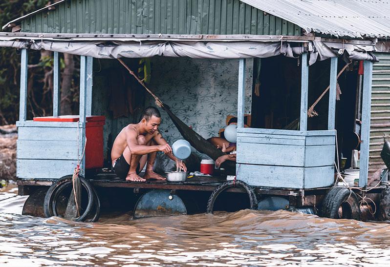 Ein Zeichen des Klimawandels: Überschwemmungen mit einem Mann vor seinem Haus
